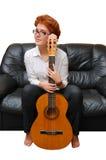 A menina Red-haired está sentando-se no sofá Fotos de Stock Royalty Free