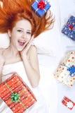 Menina red-haired feliz na cama com presentes do Natal. fotografia de stock royalty free