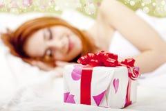 Menina Red-haired na cama com presente Foto de Stock Royalty Free