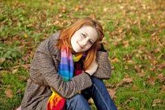 A menina red-haired nas folhas de outono. Imagens de Stock Royalty Free