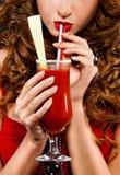 Menina Red-haired que prende um vidro do suco de tomate Fotografia de Stock Royalty Free