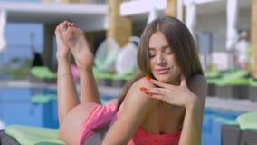 Menina relaxando, atrativa do verão no roupa de banho que descansa e que toma sol na cadeira de plataforma perto da piscina duran video estoque