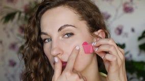 A menina remove o remendo cor-de-rosa do mordente de sua cara vídeos de arquivo
