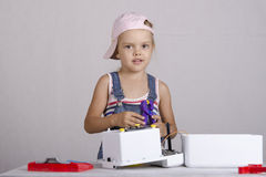 A menina repara aparelhos eletrodomésticos pequenos do brinquedo Fotografia de Stock