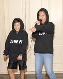 Menina resistente que executa uma música de batida com seu irmão mais novo Fotos de Stock Royalty Free