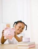 Menina responsável que põr o dinheiro no banco piggy Fotografia de Stock Royalty Free