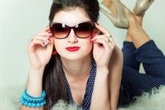 A menina retro bonita nos óculos de sol com uma curva em sua cabeça está no estúdio em um fundo azul fotos de stock royalty free