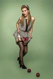 Menina retro do estilo nas meias que ferem maçãs Fotos de Stock
