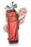 Menina retro infeliz que espreita para fora do saco de golfe vermelho de trás, isolado Fotos de Stock Royalty Free