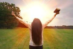 A menina reza ao deus que levanta acima das mãos acima com luz fotografia de stock