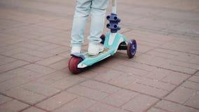 A menina rola em um 'trotinette' de três rodas através da cidade Fim acima A c?mera est? no movimento Bom modo video estoque