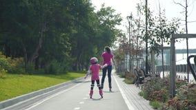 Menina Rollerblading com a mãe no parque filme