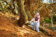 Menina romântica nova bonita que senta-se no tronco de árvore fotografia de stock