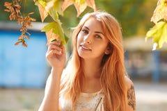 Menina ruivo bonita, alegre com folhas à disposição foto de stock