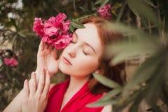 Menina ruivo bonita fechado seus olhos No assistente que guarda uma flor vermelha Retrato Imagem de Stock