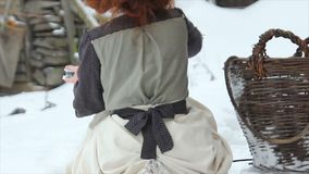 A menina ruivo bonita na roupa étnica derrama o leite para um cão em uns pires Vista traseira video estoque