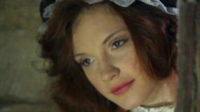 A menina ruivo bonita olha em um celeiro velho com abóboras Feriado de Dia das Bruxas filme