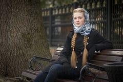 Menina ruivo bonita que senta-se em um banco imagem de stock