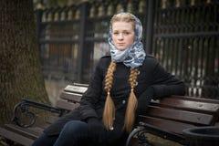 Menina ruivo bonita que senta-se em um banco imagem de stock royalty free