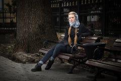 Menina ruivo bonita que senta-se em um banco fotografia de stock royalty free