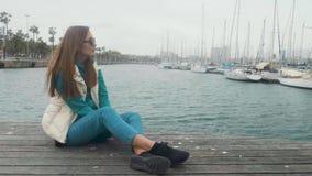 Menina ruivo bonita que senta-se no cais Contra o iate e o mar Estacionamento do navio filme