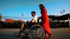 Menina ruivo bonita Rolls Guy In uma cadeira de rodas no passeio na noite video estoque