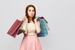 A menina ruivo bonito com bordos inflados quer comprar um vestido e pede que o noivo dê-lhe mais dinheiro para comprar Fotografia de Stock Royalty Free