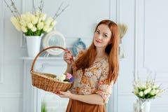 Menina ruivo bonito que guarda uma cesta das flores e que sorri, Ea imagem de stock