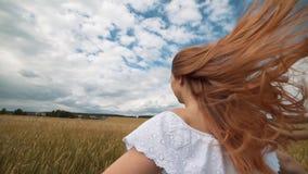 A menina ruivo em um campo de trigo em um vestido branco sorri um sorriso bonito, uma imagem perfeita para anunciar no video estoque
