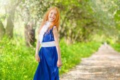 Menina ruivo em um jardim ensolarado fotografia de stock