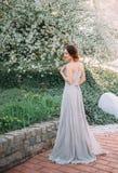 Menina ruivo em um vestido modesto, cinzento no estilo rústico Retrato da noiva no fundo de uma árvore de florescência A imagens de stock