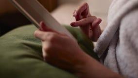 Menina ruivo em uma veste branca com uma xícara de café que senta-se em uma cama video estoque