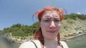A menina ruivo engraçada feliz caucasiano olha na objetiva contra o fundo do mar e da praia verde íngreme arenosa filme