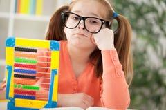 Menina ruivo furada infeliz que faz seus trabalhos de casa em casa Imagens de Stock Royalty Free