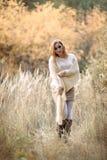 Menina ruivo na roupa leve na perspectiva da floresta do outono e das orelhas amarelas imagens de stock royalty free