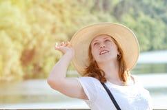 Menina ruivo no chapéu que levanta contra o fundo do rio e da floresta verde Fotos de Stock Royalty Free