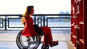A menina ruivo nova com uma inabilidade no vestido alaranjado levanta em uma cadeira de rodas à estante e toma o livro filme