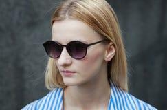 Menina ruivo nova nos óculos de sol com vidros escuros em um quadro, dia, exterior foto de stock royalty free