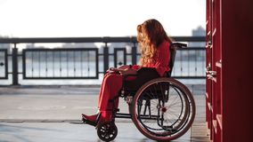 Menina ruivo nova que lê um livro em uma cadeira de rodas, na rua fotografia de stock royalty free