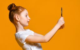 Menina ruivo pequena alegre que toma o selfie com telefone celular contra uma parede amarela fotografia de stock royalty free