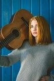 Menina ruivo que está com guitarra acústica fotografia de stock royalty free