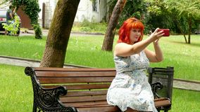 Menina ruivo que faz o selfie em um banco de parque vídeos de arquivo