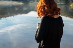 menina ruivo que realiza em suas mãos um o copo da garrafa térmica Imagem de Stock Royalty Free