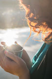 Menina ruivo que realiza em suas mãos um o copo da garrafa térmica perto do lago Fotografia de Stock Royalty Free
