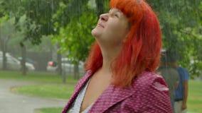 A menina ruivo torna-se molhada sob a chuva filme