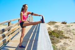 Menina running que estica em uma trilha da praia Imagens de Stock Royalty Free