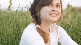 Menina rural bonita nova que senta-se em um campo na grama e no sorriso, nas emoções das mulheres e na primavera, conceito da bel video estoque