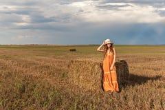 A menina rural nova encaracolado do adolescente está perto de um pacote de feno no sundress e chapéu em um campo de trigo colhido imagem de stock royalty free