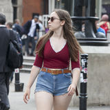 A menina séria bonita com cabelo longo em uma camisa vermelha e em um short azul cruza a estrada perto do quadrado de Leicester Fotografia de Stock