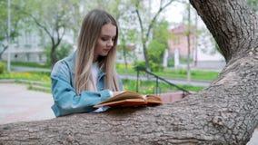 A menina séria bonita nas calças de brim revestimento e vidros lê o livro, contra o parque do verde do verão vídeos de arquivo